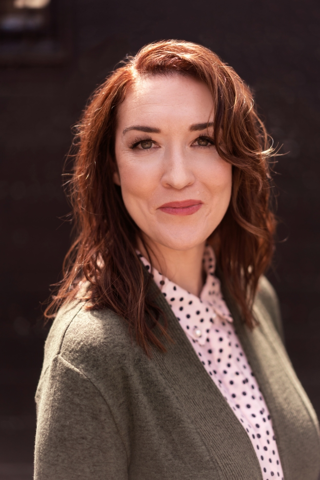 A white woman wearing a pink polka dot blouse and green sweater, with reddish-brown hair and a slightly dreamy look in her eyes, smiles close-lipped into the camera.