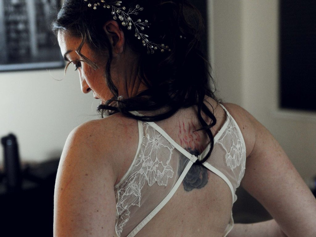 A brunette woman with pale, freckled skin, half-updo, and jeweled headdress faces away from the camera, showing a backless wedding dress with a tattoo between her shoulderblades of a black rose with flames rising from it.